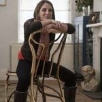 A woman sits backwards on a grown chair